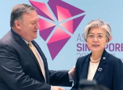 South Korean Foreign Minister Kang Kyung-wha (R) shakes hands with US Secretary of State Mike Pompeo ahead of their bilateral talks in Singapore on Aug. 4, 2018. (Yonhap)