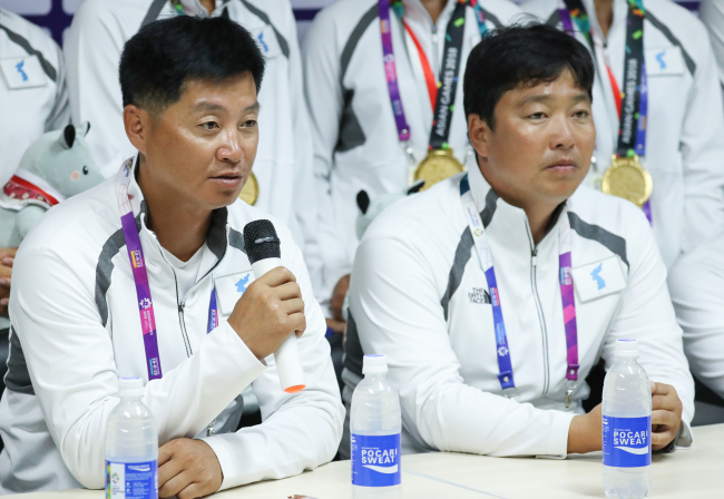 Unified Korean canoeing team coaches Kim Gwang-chol of North Korea (Left) and Kang Geun-yeong of South Korea speak at a press conference after winning gold in women's 500-meter dragon boat racing at the Jakabaring Rowing & Canoeing Regatta Course in Palembang, Indonesia, the co-host city of the Asian Games with Jakarta, on Sunday. (Yonhap)