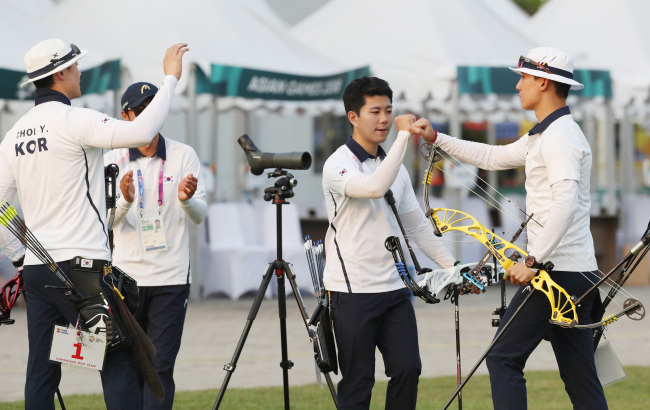 South Korean compound archers celebrate their victory over Malaysia in the men's team semifinals at the 18th Asian Games at GBK Archery Field in Jakarta on Sunday. (Yonhap)