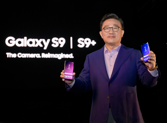 Koh Dong-jin, the CEO of Samsung Electronics' mobile business division, poses with the Galaxy S9 and Galaxy S9 Plus at the launch event of the smartphones in February 2018.