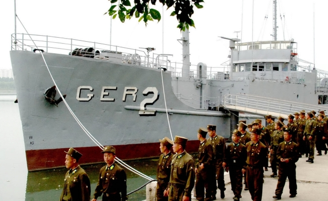 File photo showing North Korean soldiers looking at the US spy ship Pueblo, which was seized on Jan. 23, 1968, and is displayed at the Daedong river in Pyongyang. (Yonhap)