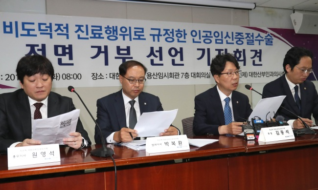 Kim Dong-suk (second from right), the head of the Korean College of Ob & Gyn, attends a press conference along with his colleagues in Seoul, Tuesday. (Yonhap)