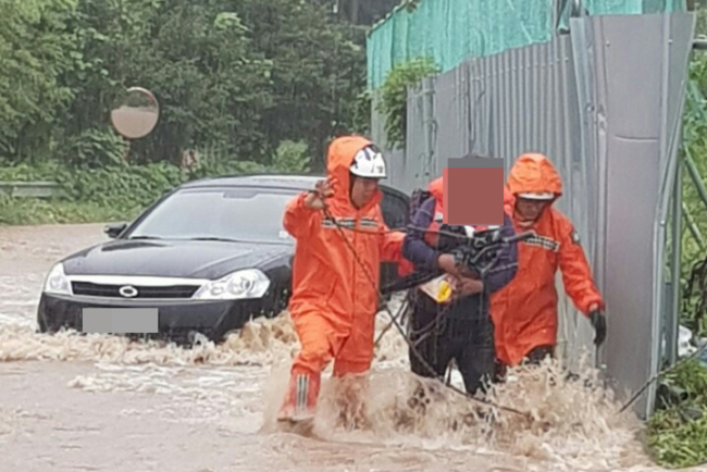 Firefighters rescue a driver in his 50s, who was stranded in a deluge in Eumseong County, North Chungcheong Province, Tuesday. (Yonhap)