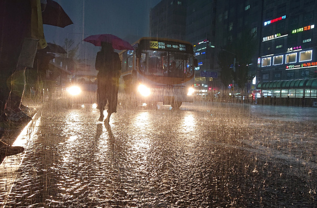 A commuter waits for a bus in Goyang, Gyeonggi Province on Tuesday in torrential rain.(Yonhap)