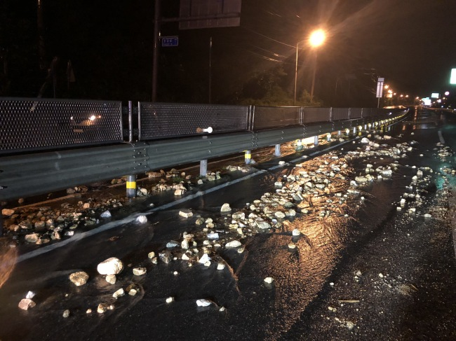 The photo on Aug. 30, captures rocks scattered on a road in Yangju, Gyeonggi Province, about 25 km north of Seoul, due to rockslides as heavy rains battered the region. (Yonhap)