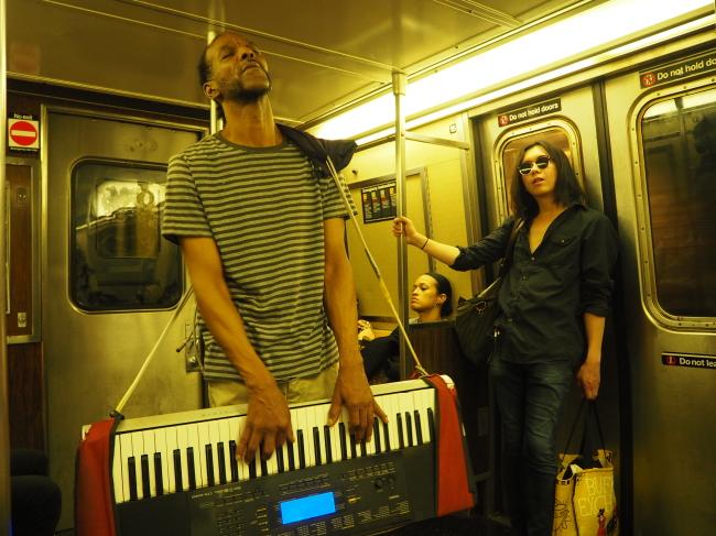 An artist performs live music inside an NYC subway car. (Joel Lee/The Korea Herald)