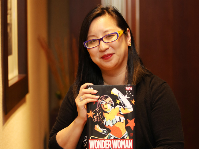 "Amy Chu poses with her ""Wonder Woman"" comic book before an interview with The Korea Herald on Wednesday in central Seoul. (CICI)"