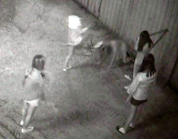 In surveillance camera footage, a schoolgirl victim is on her hands and knees as she is kicked in the head by one of four attackers. (Yonhap)