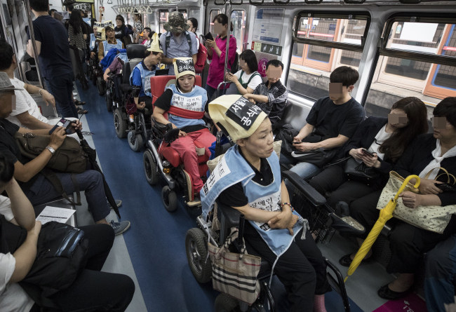 South Koreans with disabilities protest Seoul`s public transportation system, which they claim to be unsafe and non-inclusive, inside a Seoul Metro train in July (Yonhap)