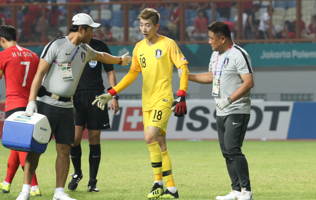 Jo Hyeon-woo (center) is replaced during a round of 16 match against Iran with a knee injury at the 18th Asian Games at Wibawa Mukti Stadium in Cikarang, Indonesia, Aug. 23. (Yonhap)