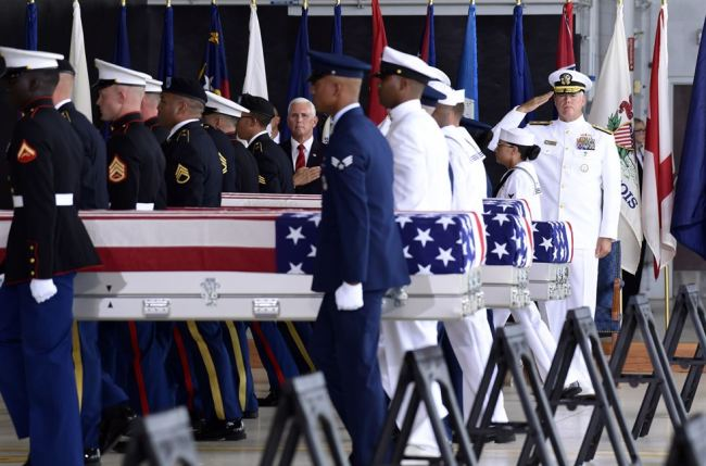 US Vice President Mike Pence and Navy Rear Adm. Jon Kreitz, deputy director of the POW/MIA Accounting Agency, right, watch as military members carry transfer cases from a C-17 at a ceremony marking the arrival of the remains believed to be of American service members who fell in the Korean War at Joint Base Pearl Harbor-Hickam, Hawaii, on Aug. 1. (AP-Yonhap)