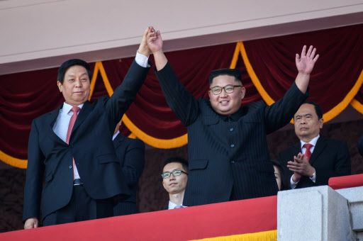 North Korea`s leader Kim Jong Un (R) waves with China`s Chairman of the Standing Committee of the National People`s Congress Li Zhanshu (L) from a balcony of the Grand People`s House on Kim Il Sung square following military parade and mass rally on September 9, 2018. (AFP)