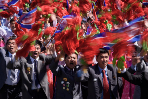 Participants wave flowers as they march past a balcony from where North Korea`s leader Kim Jong Un was watching, during a mass rally on Kim Il Sung square in Pyongyang on September 9, 2018. - North Korea held a military parade to mark its 70th birthday, but refrained from showing off the intercontinental ballistic missiles that have seen it hit with multiple international sanctions. (AFP)