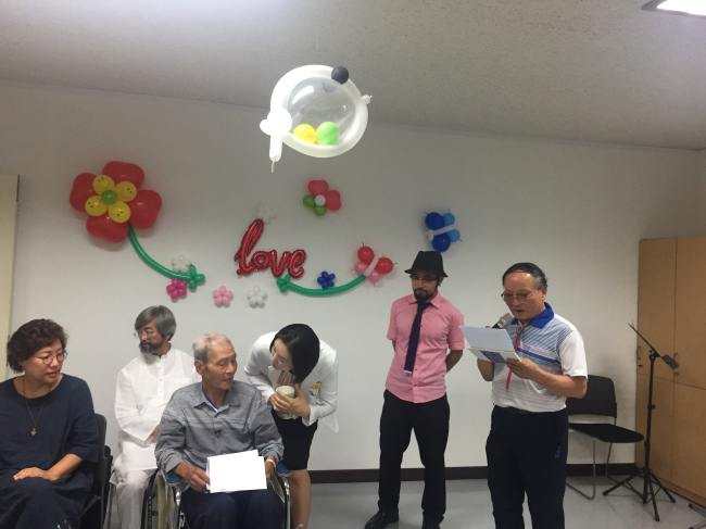 Kim Byung-guk (in wheelchair) listens to his colleague Kim Sun-tae (far right)`s speech during his own funeral at Seoul Metropolitan Dongbu Hospital on Aug. 14. (Claire Lee/ The Korea Herald)