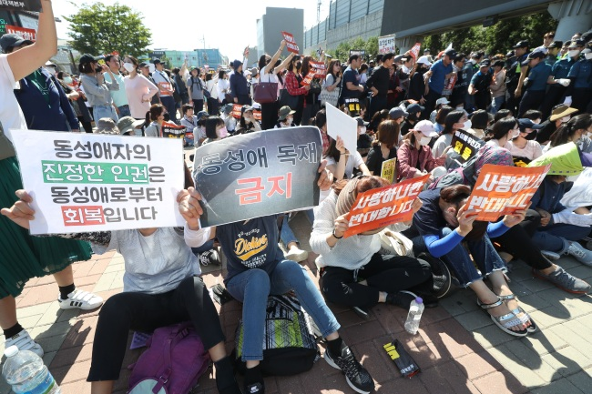 Anti-gay protesters hold signs at the first edition of queer festival held in Incheon, about 50 km west of Seoul, on Saturday (Yonhap)