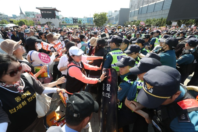 Anti-gay protesters clash with the police as they try to block LGBT Koreans from holding a queer festival in Incheon on Saturday. (Yonhap)