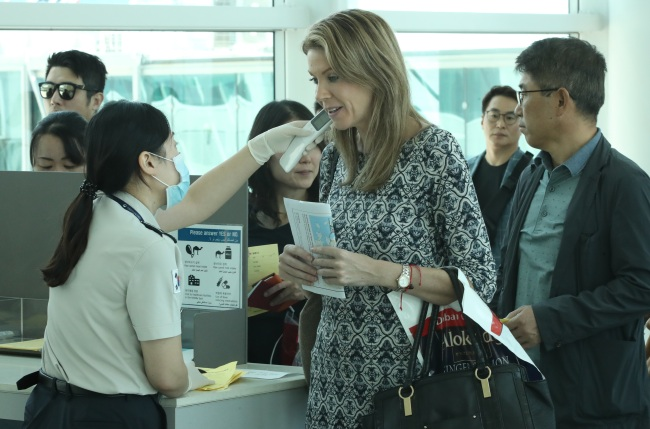 Travellers are being inspected for fever upon their arrival at South Korea`s Incheon International Airport on Monday. (Yonhap)