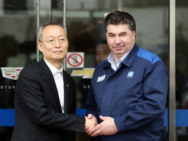 Trade Minister Paik Un-gyu (left) and Kaher Kazam, CEO of GM Korea, shake hands in front of GM Korea's Bupyeong plant in Incheon on April 6. (Yonhap)