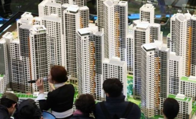 In this photo taken March 16, visitors look at a model of DH Xi Gaepo apartment buildings in southern Seoul. (Yonhap)