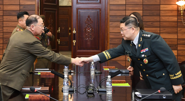 South Korea`s delegate chief Col. Cho Young-keun shakes hands with his North Korean counterpart Um Chang-nam during the military talks at Panmunjom on Thursday. Yonhap