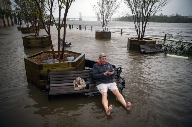 Ray Baca, from Wilmington, North Carolina, checks his phone as he sits on a bench, as the Cape Fear River flows onto South Water St., after Hurricane Florence made landfall, September 14, 2018 in Wilmington, North Carolina.(Yonhap)