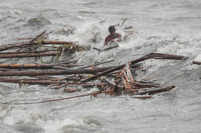 A man is hit by a wave while attempting to recover salvageable materials in Manila Bay, Manila, Philippines, Saturday. (Yonhap)