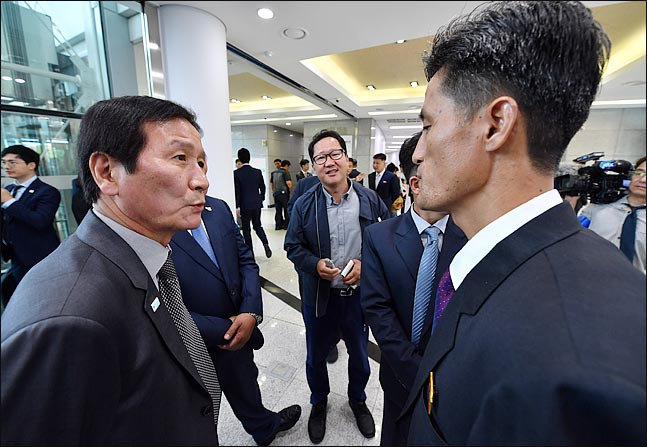 Chung Ki-sub (left), honorary chairman of the Corporate Association of the Kaesong Industrial Complex, talks with a North Korean official at the opening ceremony for the joint liaison office in the North's Kaesong, North Hwanghae Province, Friday. (Joint Press Corps)