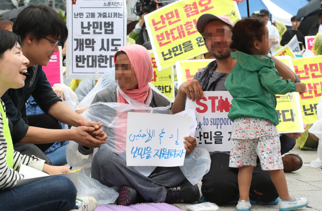 An asylum-seeking family participates in the rally in support of refugees in Jongno, central Seoul, Sunday. (Yonhap)