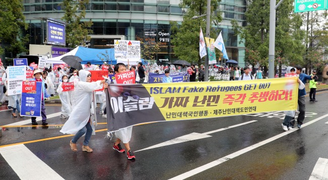 Anti-refugee protesters march to the National Human Rights Commission while demanding abolishment of the Refugee Act, in Jongno, central Seoul on Sunday. (Yonhap)