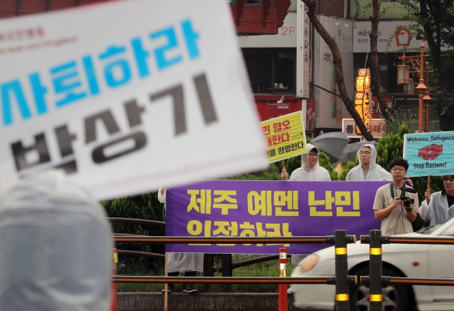 """One placard (front) reads, """"Step Down, Justice Minister Park Sang-ki,"""" while the other reads, """"Accept Yemeni asylum seekers on Jeju as refugees,"""" in the streets of Jongno, central Seoul on Sunday. (Yonhap)"""