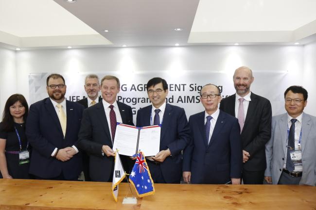 LIG Nex1 CEO Kim Ji-chan (fifth from left) and Rob Hawkets (fourth from left), vice president of KBR Government Services Asia Pacific, pose at a signing ceremony during the industry exhibition DX-Korea 2018 at Kintex in Goyang, Gyeonggi Province, Thursday. (LIG Nex1)