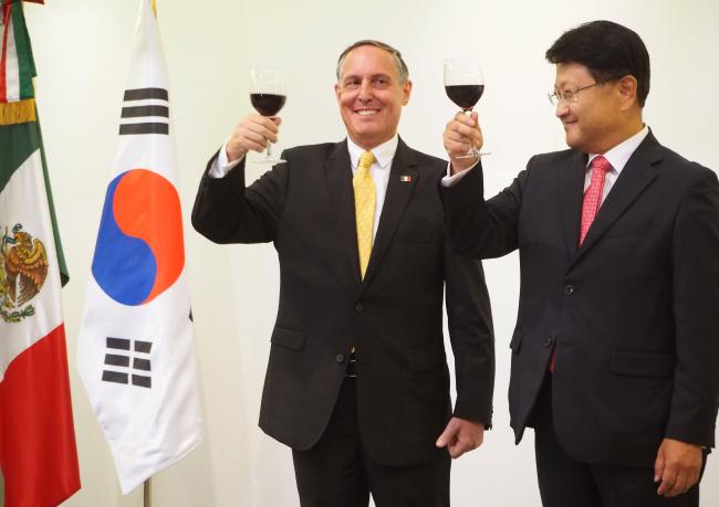 Mexican Ambassador to Korea Bruno Figueroa Fischer (left) raises his glass with Korean Deputy Minister for Public Diplomacy Park Sahng-hoon at a reception Friday. (Joel Lee/The Korea Herald)