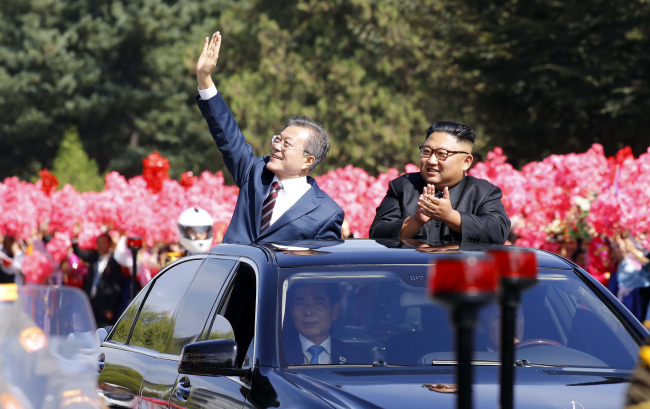 South Korean President Moon Jae-in (left) and North Korean leader Kim Jong-un wave at a cheering crowd in Pyongyang on Tuesday, ahead of their summit. (Joint Press Corp.)