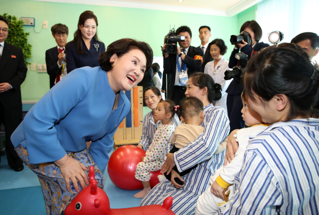 South Korea`s first lady Kim Jung-sook (front) talks to North Korean children at the Okryu Children's Hospital in Pyongyang on Tuesday, alongside North Korea`s first lady Ri Sol-ju (back). (Joint Press Corps)