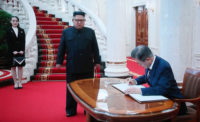 North Korean leader Kim Jong-un stands by a desk while Moon Jae-in writes his name on the visitors' log at the headquarters of the Central Committee of the Workers' Party of Korea in Pyongyang on Tuesday, ahead of their summit. (Joint Press Corp.)