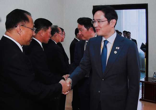 North Korean economy chief Ri Ryong-nam (left) shakes hands with Samsung Electronics heir Lee Jae-yong at People's Culture Palace in Pyongyang on Tuesday. (Joint Press Corp)