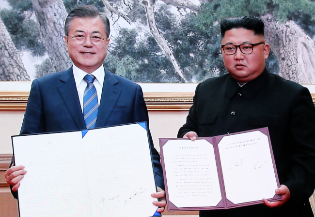 South Korean President Moon Jae-in (left) and North Korean leader Kim Jong-un hold up the signed agreement of the Pyongyang Declaration after holding the second round of the inter-Korean summit on Wednesday. (Joint Press Corp.)
