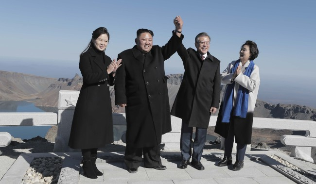 The leaders of the two Koreas and their wives pose for a photo in front of Chonji on Paektusan, North Korea, Thursday. (Joint Press Corp.)