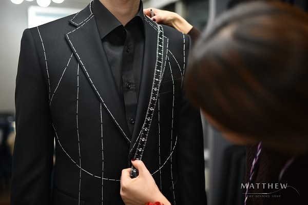 Kang measures the length of a jacket lapel. (Matthew)