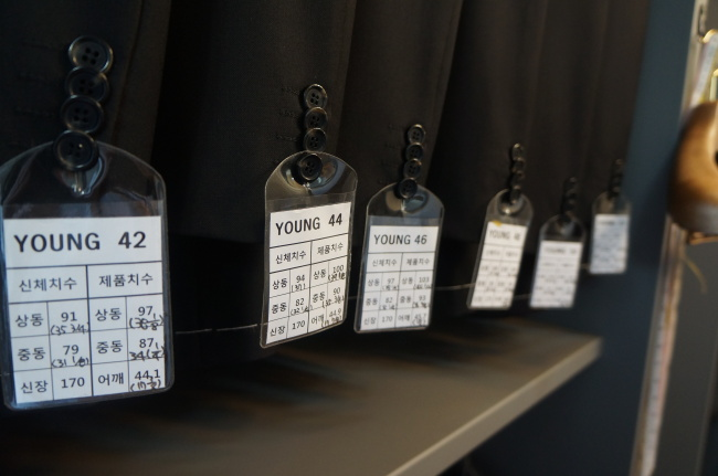 Tags that include customers' body size information hang on tailored jackets. (Im Eun-byel/The Korea Herald)