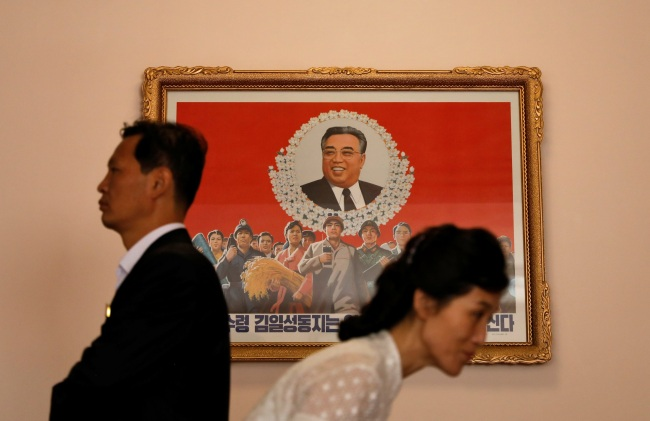Pyongyang residents walk past an image of late North Korean leader Kim Il Sung at a teachers` training college in Pyongyang, North Korea, on Sept. 7. (Yonhap)