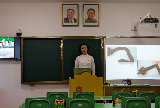 A student stands under the portraits of late North Korean leaders Kim Il Sung and Kim Jong Il during a lecture at a teachers` training college in Pyongyang. (Yonhap)