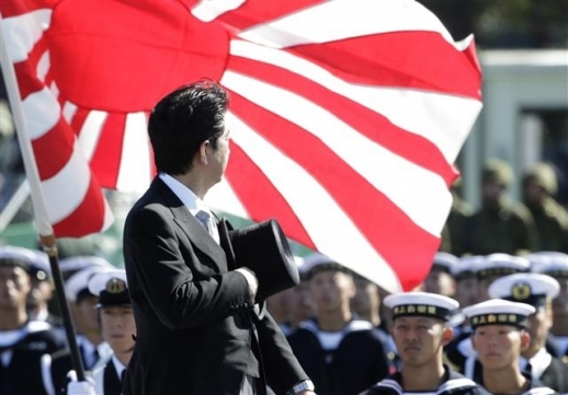 Japanese Prime Minister Shinzo Abe pays respect to Rising Sun Flag during a military ceremony. Yonhap
