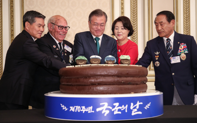President Moon Jae-in and first lady Kim Jung-sook cut a cake shaped like a choco pie at an event held to commemorate the 70th Armed Forces Day at Cheong Wa Dae on Monday. (Yonhap)