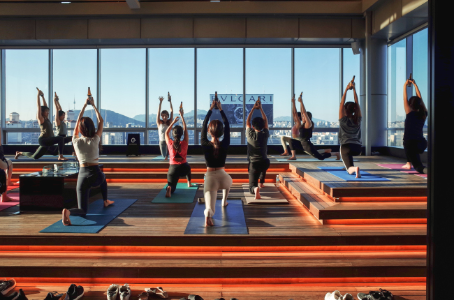 Participants practice the sun salutation pose with a beer in their hands during a beer yoga lass. (Almondon)