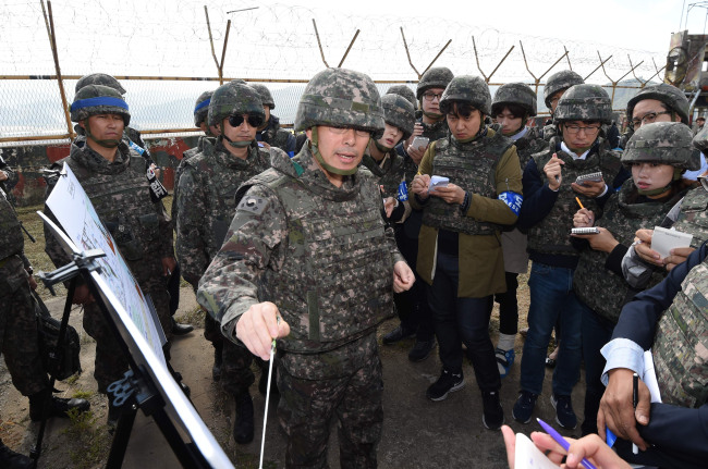 An Army general commanding the demining operation briefs reporters about the location of buried mines and the procedure to search for them. Yonhap