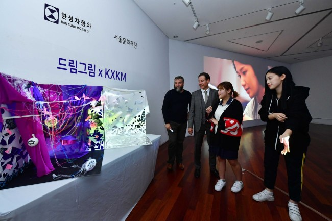 "Students taking part in the Dream Gream project explain their work to Han Sung Motor CEO Ulf Ausprung (second from left) at the opening ceremony of ""A new message has arrived,"" part of this year's Seoul Street Arts Festival, held earlier this week in northern Seoul. (Han Sung Motor)"