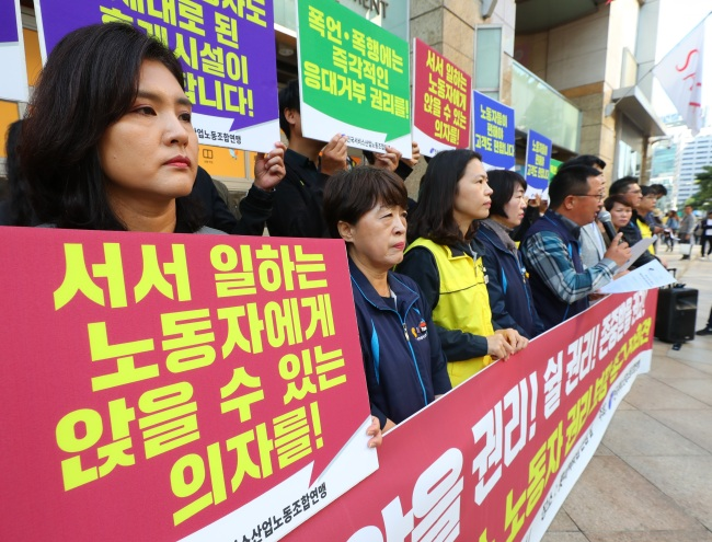 Unionized workers in Korea`s service sector hold signs that read