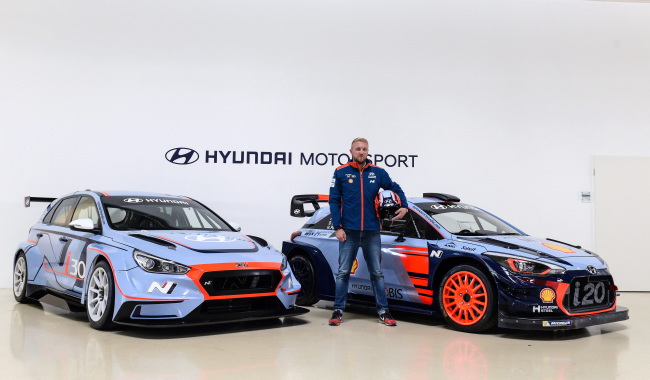 A racer poses between the i30 N TCR (left) and i20 Coupe WRC.