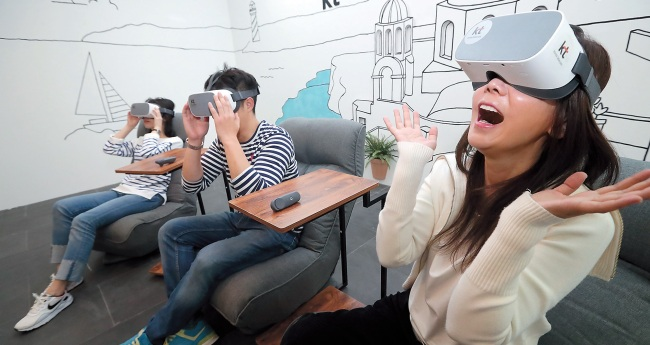 Visitors watch a virtual reality film at VR Movie Live zone set up by KT during the Busan International Film Festival on Thursday. (Yonhap)